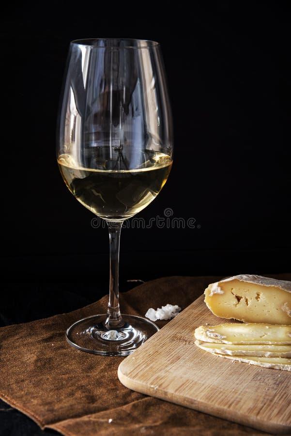 Um vidro do vinho branco e do queijo caseiro imagens de stock royalty free