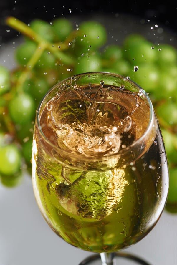 Um vidro do vinho branco em um fundo das uvas Respingo de alta velocidade do vinho Foco seletivo fotografia de stock royalty free