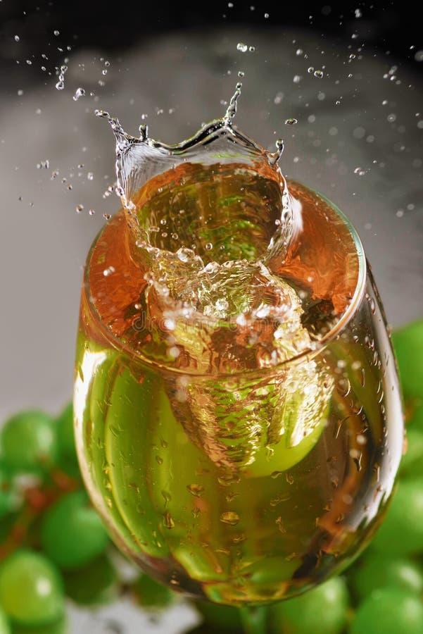 Um vidro do vinho branco em um fundo das uvas Respingo de alta velocidade do vinho Foco seletivo imagem de stock