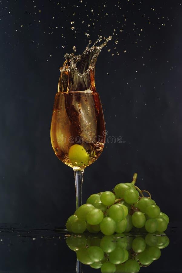 Um vidro do vinho branco em um fundo escuro Vinho branco do respingo Grupo da uva fotos de stock royalty free