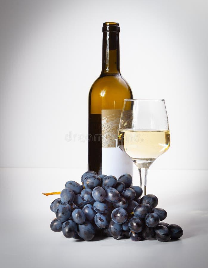 Um vidro do vinho branco, um grupo de uvas, uma garrafa aberta fotografia de stock royalty free