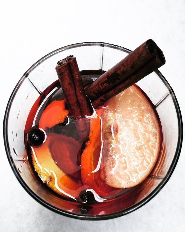 Um vidro do vinho ferventado com especiarias na neve foto de stock
