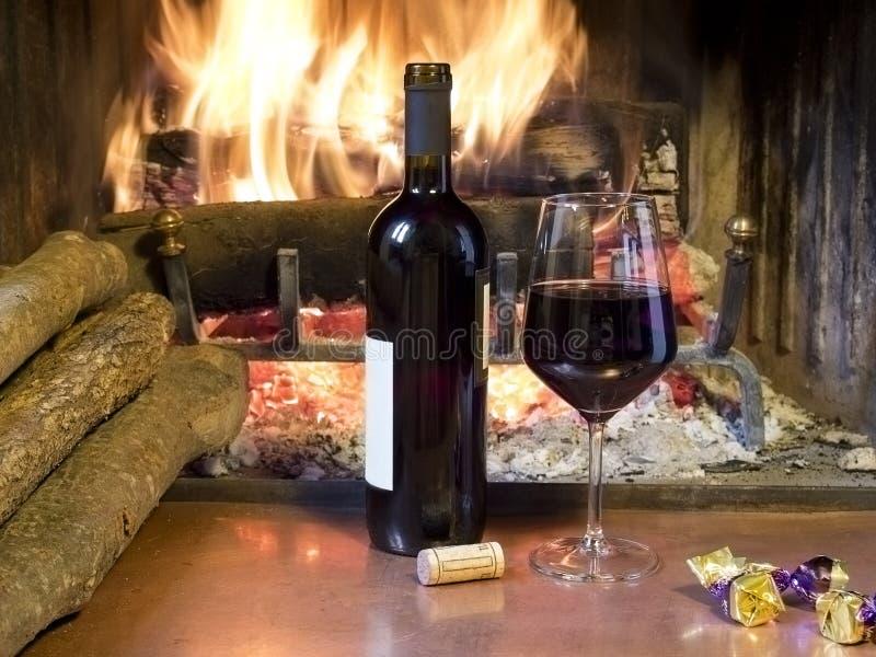 Um vidro do vinho na frente de uma chaminé imagem de stock