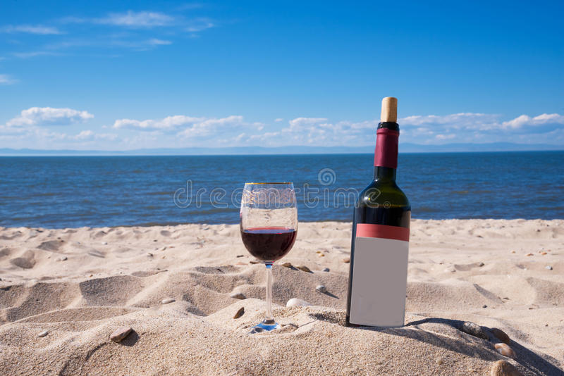 Um vidro do vinho tinto e de uma garrafa na praia em um dia ensolarado do verão Mar e céu azul no fundo imagem de stock royalty free