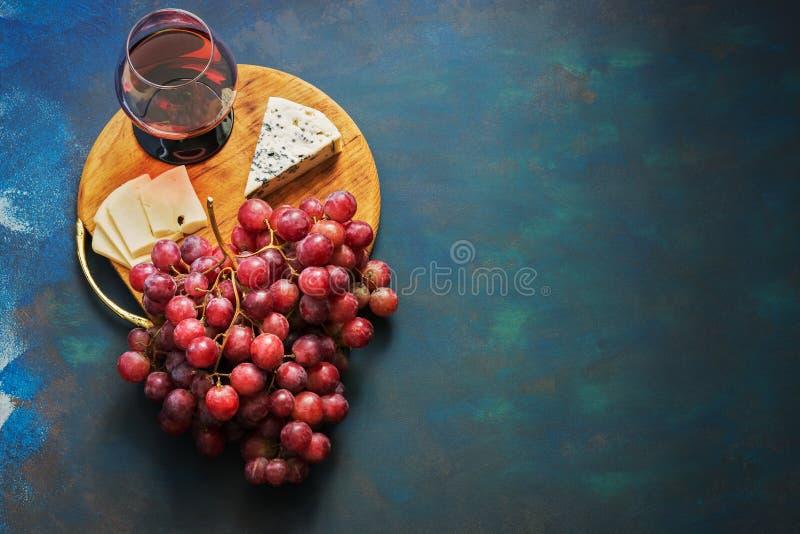 Um vidro do vinho tinto, uvas, queijo, queijo azul em uma placa de corte, fundo azul Vista superior, espaço da cópia foto de stock