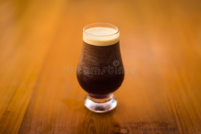 Um vidro frio da cerveja escura em uma superfície de madeira foto de stock