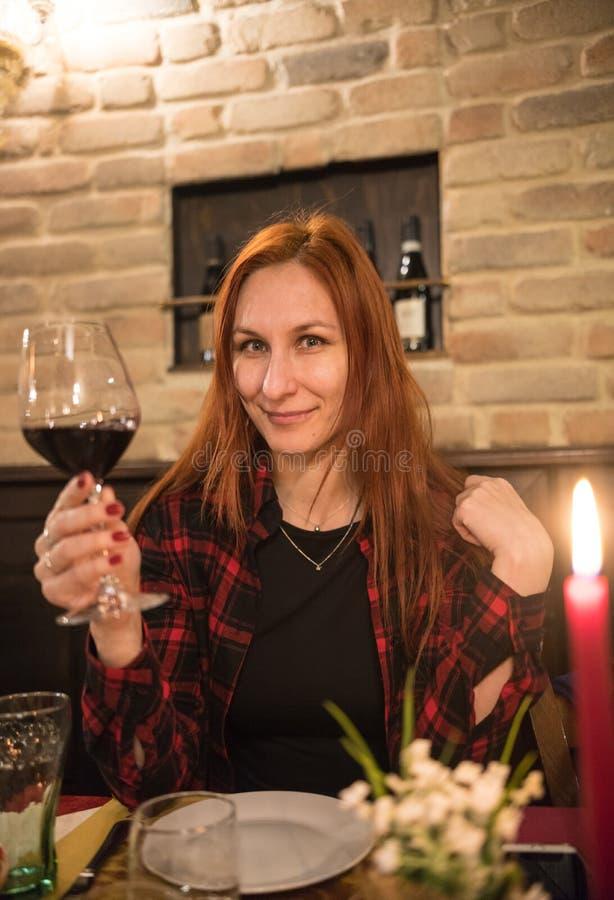Um vinho bebendo da mulher em um restaurante imagens de stock royalty free