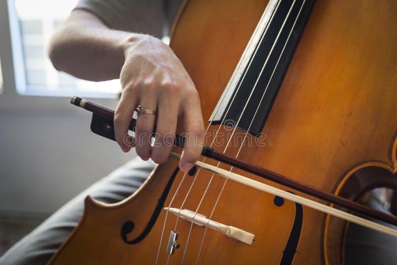 Um violoncelo que está sendo jogado pelo executor imagens de stock royalty free