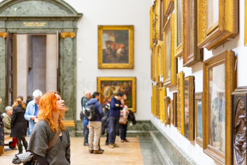 Um visitante fêmea que admira as pinturas indicadas em Tate Britain fotografia de stock royalty free