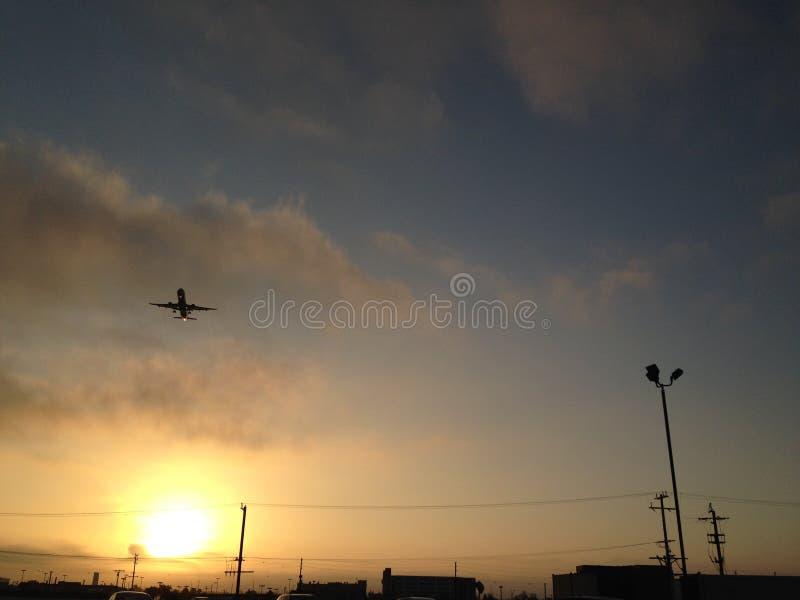 Um voo do avião longe do nascer do sol foto de stock royalty free