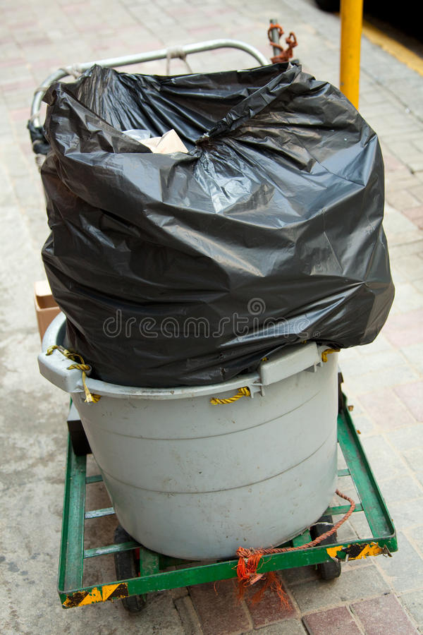 Um wheelie-escaninho com um saco de lixo plástico preto imagens de stock