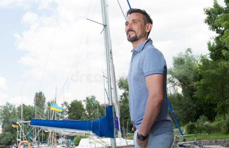Um 'yachtsman' que passa o tempo livre antes da viagem que anda no porto e que olha sightseeing durante férias frescas do verão imagens de stock