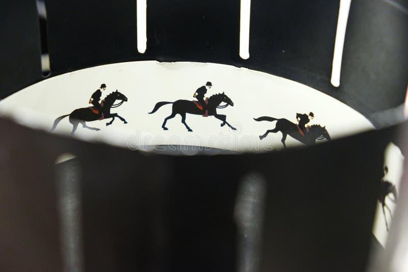 Um zoetrope é os dispositivos da animação do filme que produzem a ilusão do movimento indicando o movimento dos desenhos Foto ilu fotos de stock