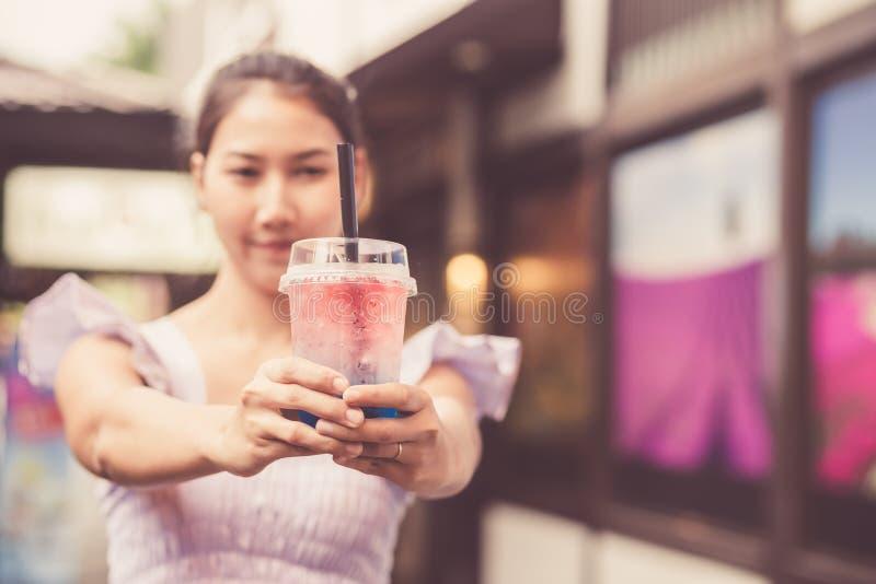 Uma água de vidro da mostra da menina no mercado fotografia de stock royalty free