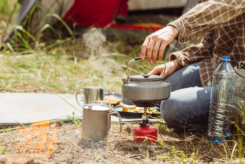 Uma água a ferver da pessoa sobre um fogão do propano para fazer o chá imagens de stock