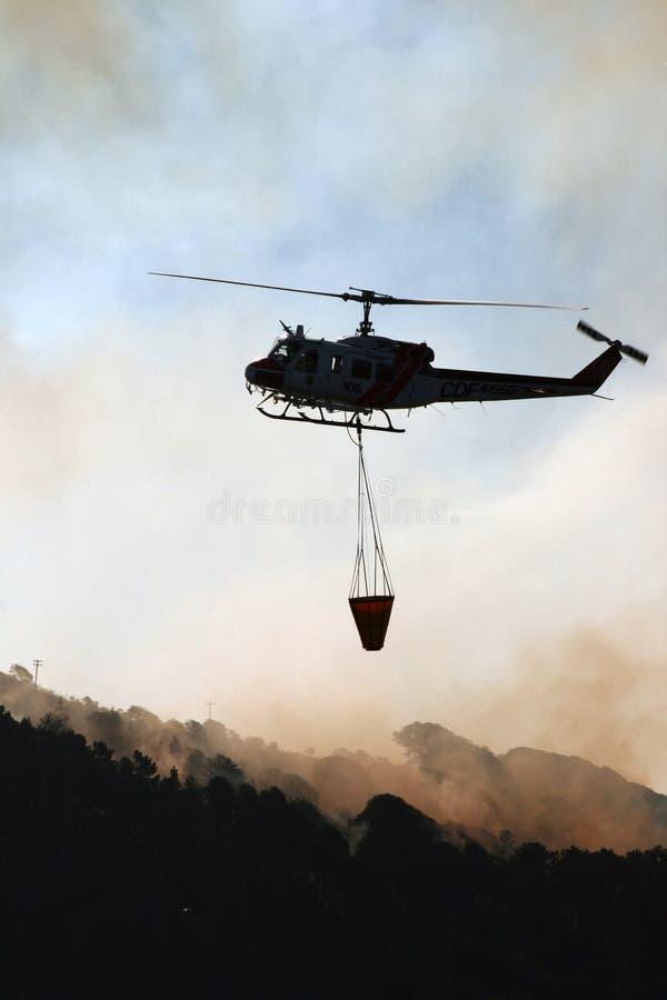 Uma água levando do helicóptero para pôr para fora um incêndio violento fotografia de stock