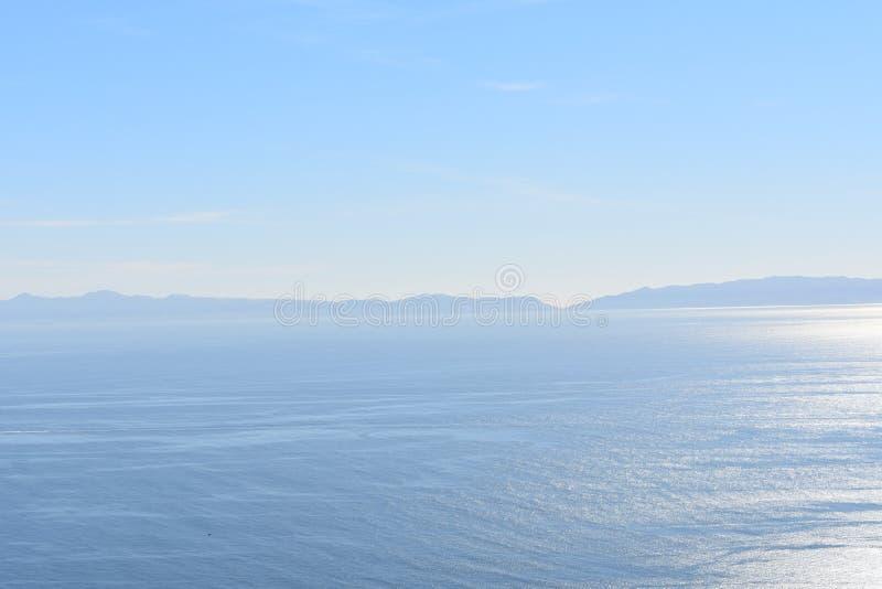 Uma água lisa calma de Sunny Ocean View With e um céu azul claro fotografia de stock royalty free