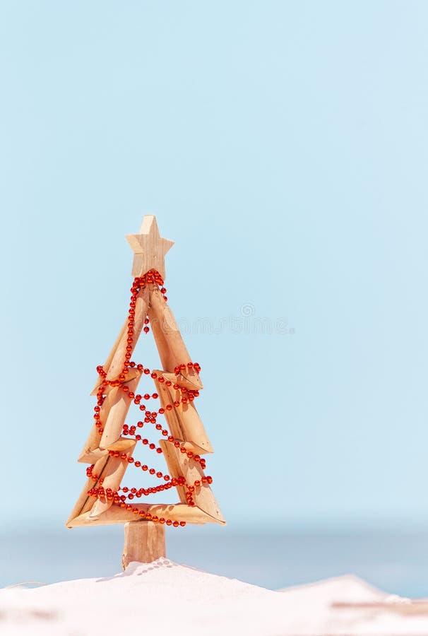 Uma árvore de Natal de madeira decorada com suportes vermelhos das quinquilharias na praia em Austrália Espaço para a cópia fotos de stock royalty free