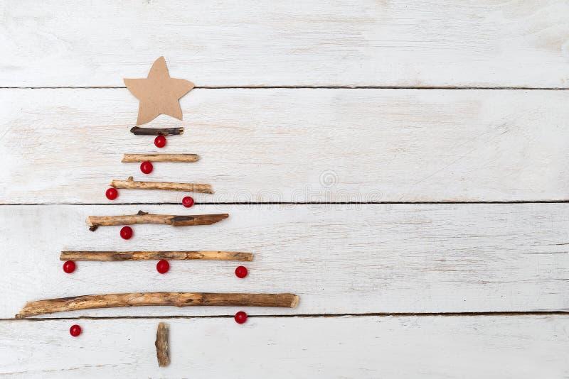 Uma árvore de Natal de madeira e as bagas de um viburnum em um branco cortejam imagem de stock royalty free