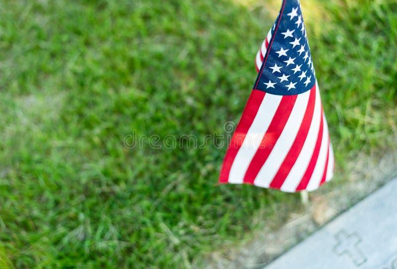 Uma única bandeira americana colocada em um marcador do gravesite do ` s do veterano fotografia de stock royalty free