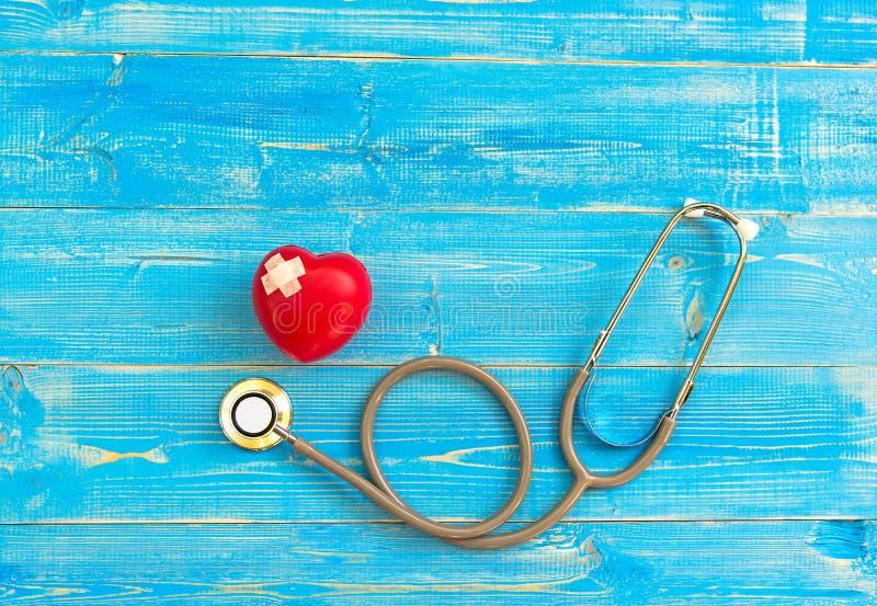 Uma única bola vermelha sozinha do exercício da mão da forma do amor do coração com o backgro de madeira azul do estetoscópio do  fotos de stock