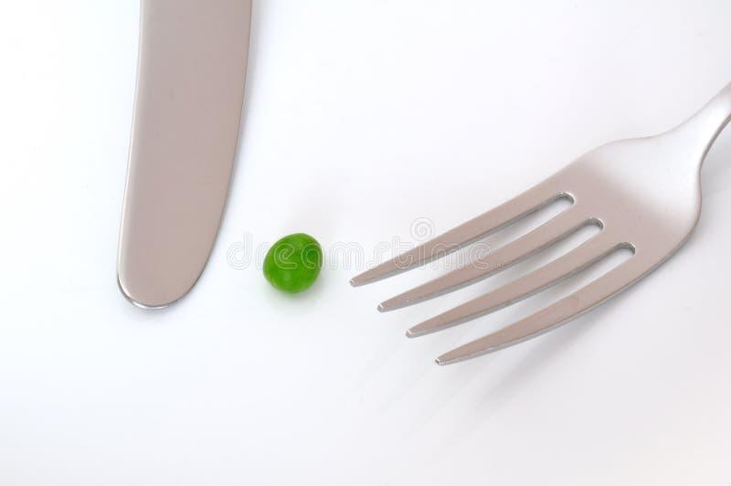 Uma única ervilha, uma faca, e uma forquilha imagem de stock