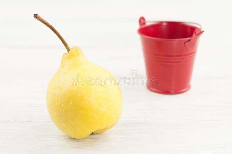 Uma única pera inteira madura amarela fresca e cubeta vermelha vazia do metal imagens de stock