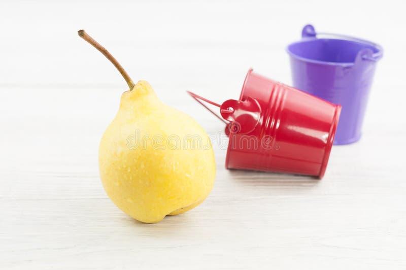 Uma única pera inteira madura amarela fresca e cubetas vermelhas e violetas vazias do metal fotografia de stock