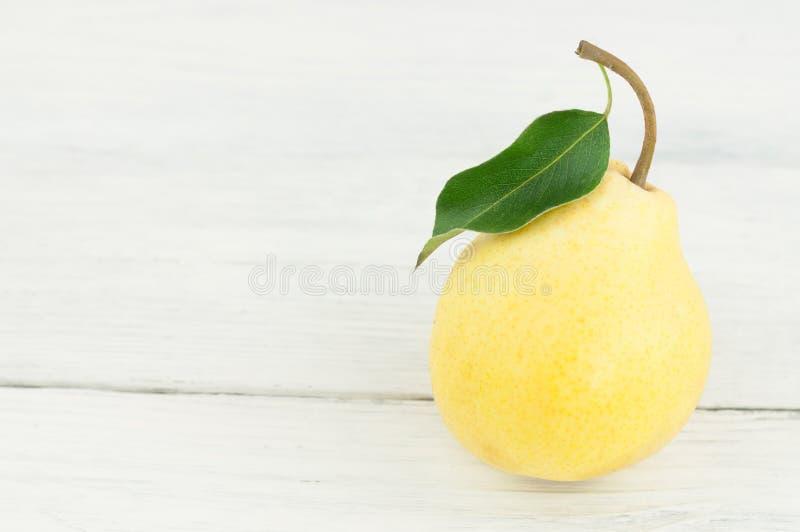Uma única pera madura inteira fresca com folha verde fotografia de stock royalty free