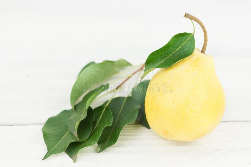 Uma única pera madura inteira fresca com folhas verdes foto de stock royalty free