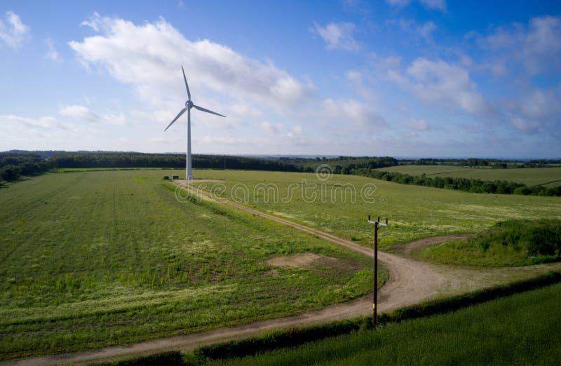 Uma única turbina eólica que está em um campo imagens de stock royalty free