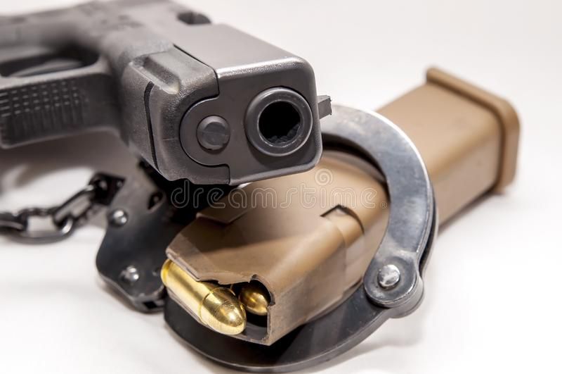 Uma algema preta com um compartimento marrom da pistola nele com uma pistola preta de 9mm que coloca sobre ela foto de stock