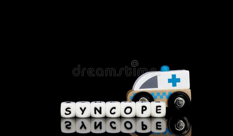 uma ambulância do brinquedo e um síncope da palavra imagens de stock royalty free