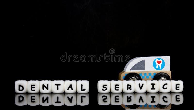 uma ambulância do brinquedo e um serviço dental da palavra fotografia de stock