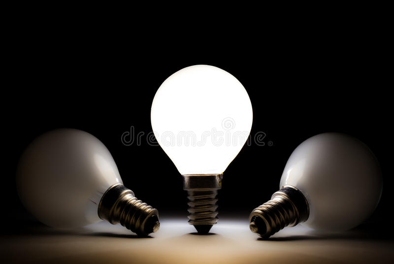 Uma ampola que brilha outros bulbos inoperantes imagem de stock