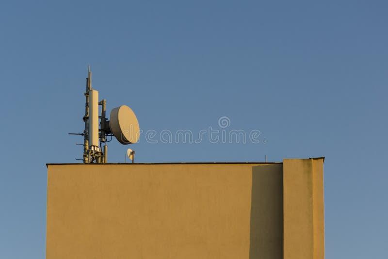 Uma antena das telecomunicações da televisão no céu azul claro do dia montado no telhado da construção quadrada amarela como um f foto de stock royalty free