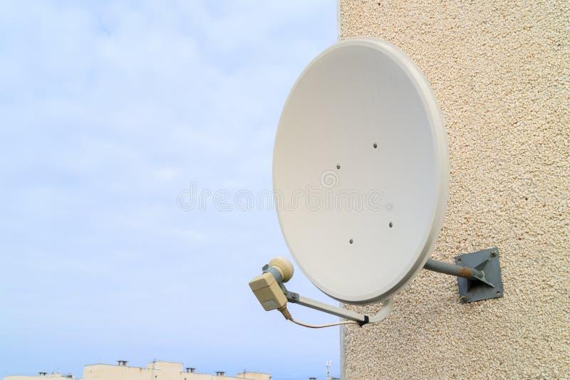 Uma antena parabólica para receber o sinal da tevê é aparafusada à parede branca fotografia de stock