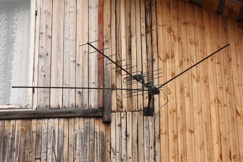 Uma antena preta grande com um fio na parede de uma casa de moradia com uma janela branca fotografia de stock