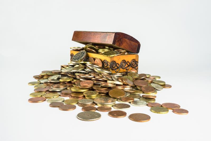 Uma arca do tesouro de madeira pequena que esteja estourando com moedas foto de stock royalty free