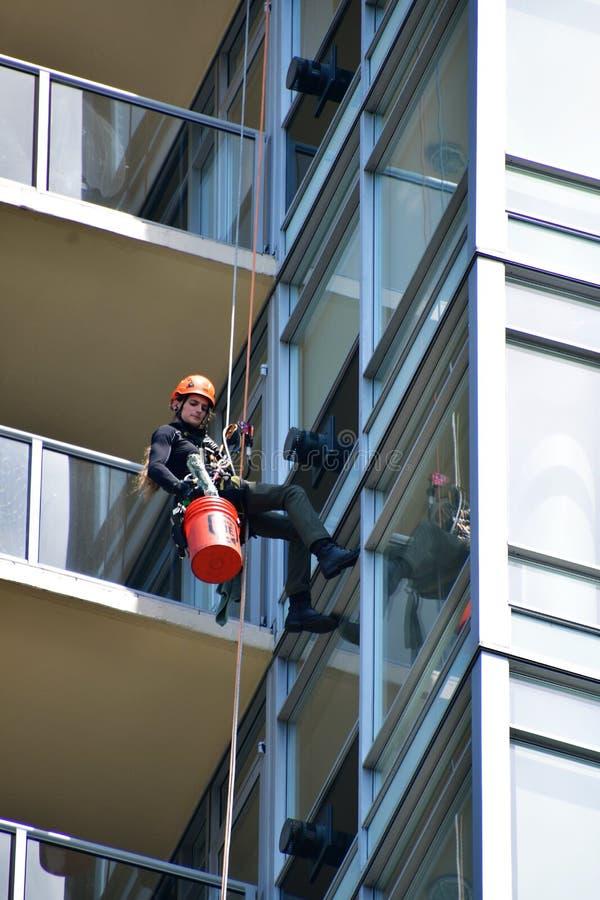 Uma arruela de janela que limpa a janela de uma construção alta da elevação imagem de stock royalty free