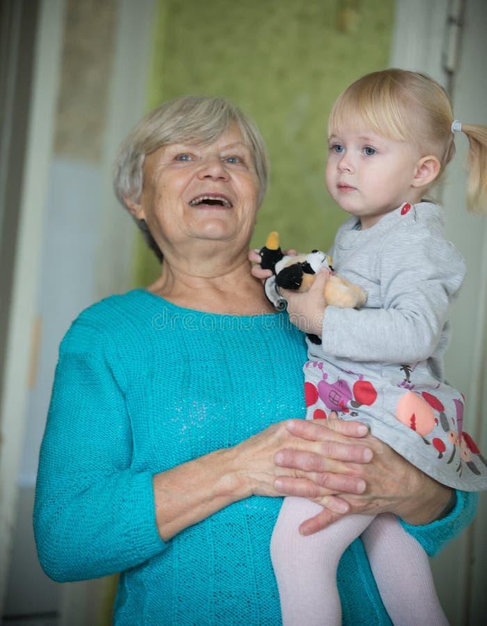 Uma avó de sorriso que guarda um bebê pequeno imagem de stock royalty free