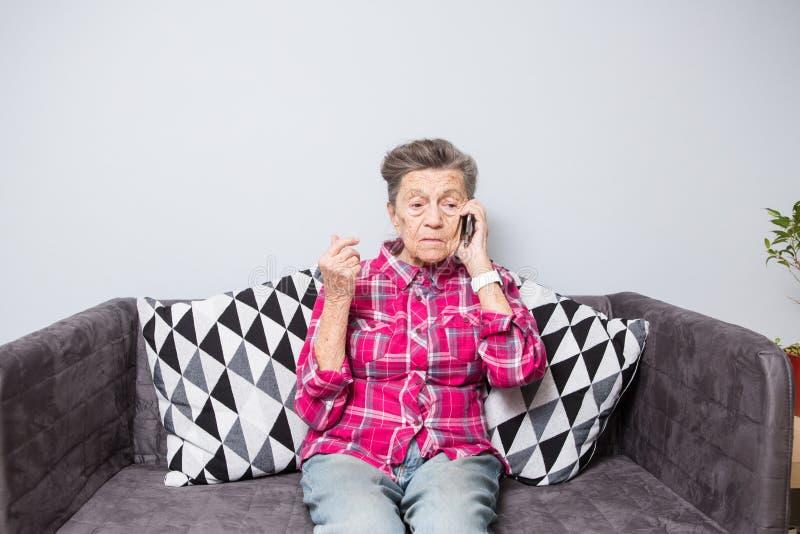Uma avó idosa idosa da mulher com cabelo cinzento senta-se em casa no sofá usando o telefone da mão, uma conversação telefô fotos de stock