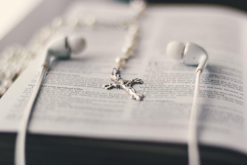Uma Bíblia está aberta colocado em uma tabela com uma cruz e earbuds imagem de stock