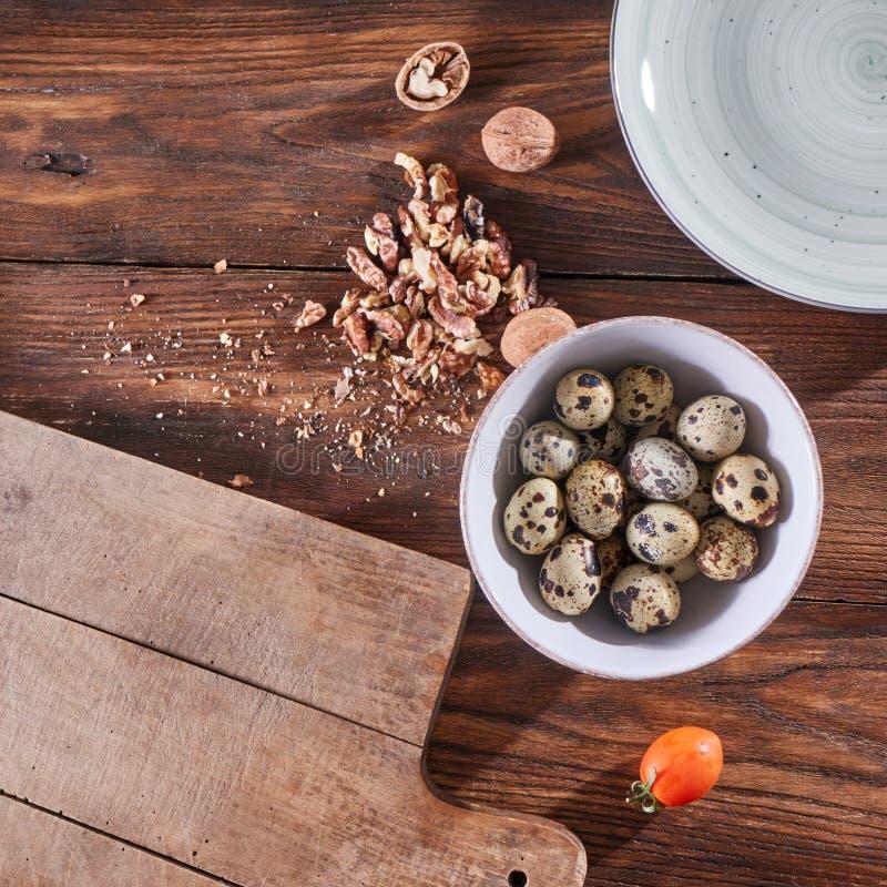 Uma bacia com ovos de codorniz, partes de noz e uma placa de madeira na mesa de cozinha com espaço da cópia Ingredientes para imagens de stock