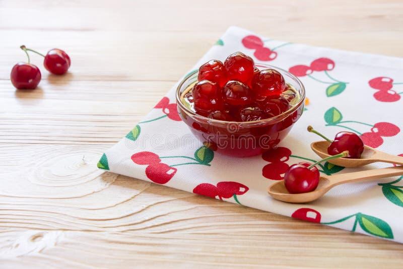 Uma bacia de cereja adoçada frutifica em um guardanapo com cerejas, espaço da cópia fotos de stock