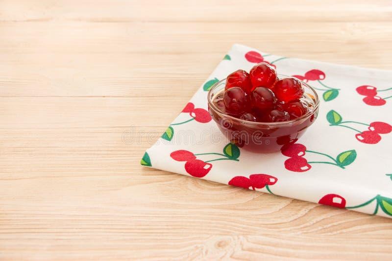 Uma bacia de cereja adoçada frutifica em um guardanapo com cerejas, espaço da cópia imagem de stock