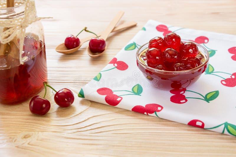 Uma bacia de cereja adoçada frutifica em um guardanapo com cerejas, espaço da cópia imagens de stock