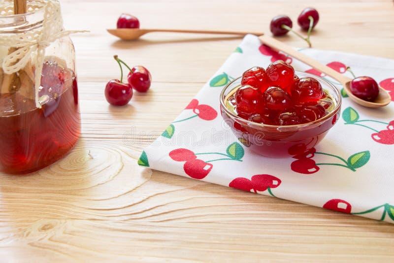 Uma bacia de cereja adoçada frutifica em um guardanapo com cerejas, espaço da cópia foto de stock