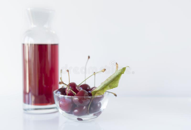 Uma bacia de cereja com uma garrafa em um fundo branco, fim acima, isolado imagem de stock royalty free