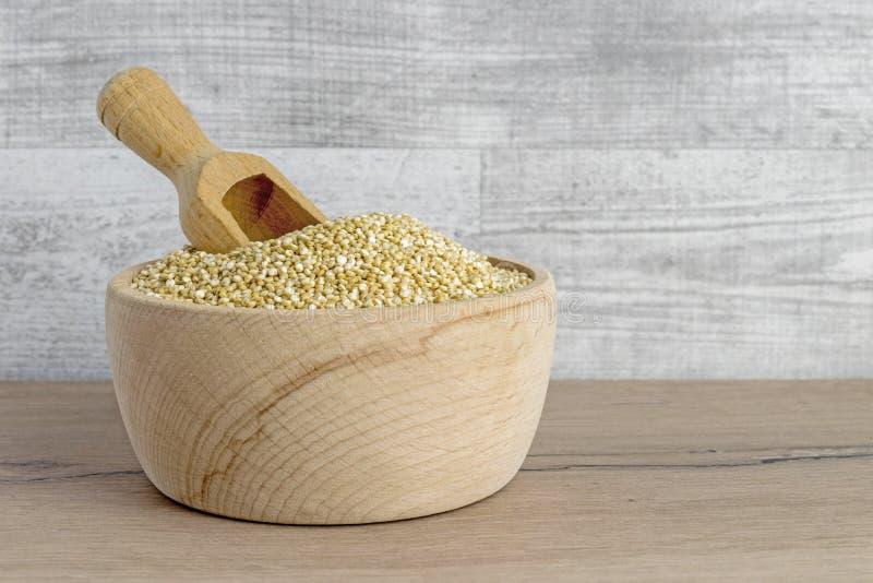 Uma bacia de madeira de sementes e de colher do quinoa imagem de stock royalty free